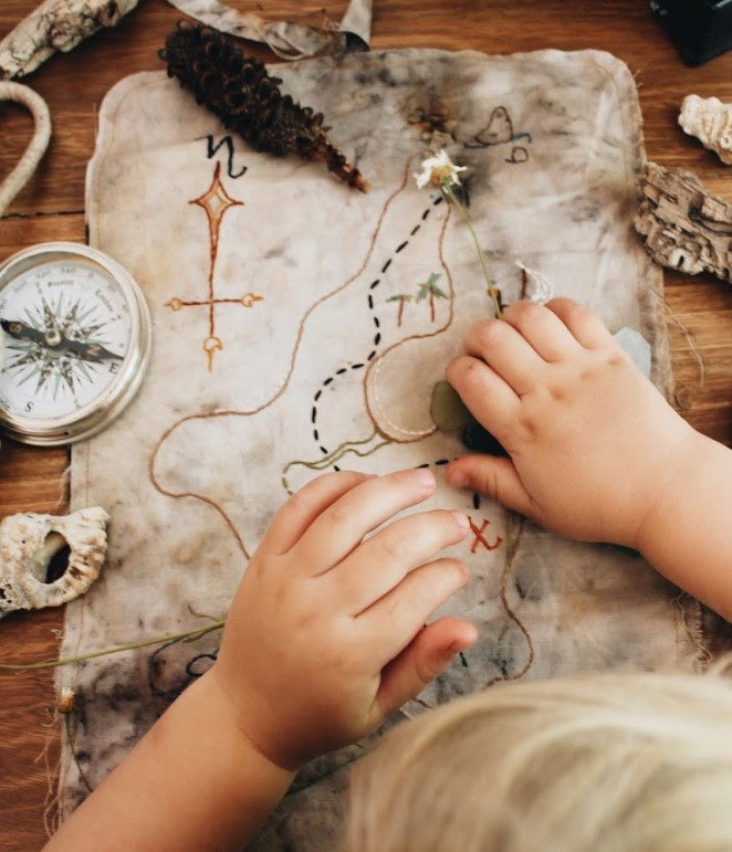 A pirate map sits on a desk with seed pods. driftwood, a compass and some sea glass surrounding it. two little toddler hands and a wisp of blonde curls are above the map, reading it's directions.