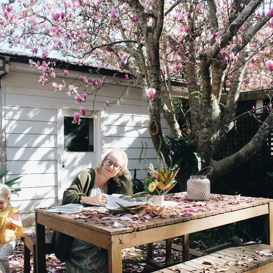 a lady wearing black rimmed glasses sits at a wooden table. there is a magnolia tree in full blossom and pink petals everywhere. She is drawing.