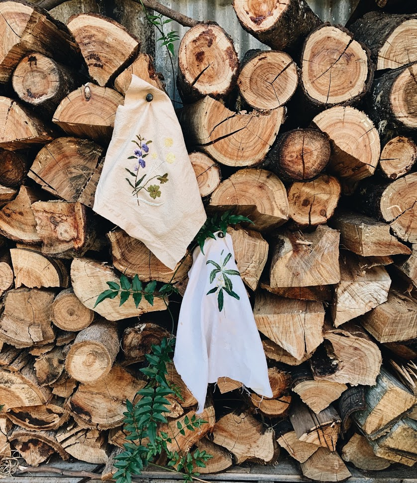A close up of logs chopped in a wood stack. pinned to this is two pieces of cloth, each with florals embroidered on them. A green vine creeps along through.