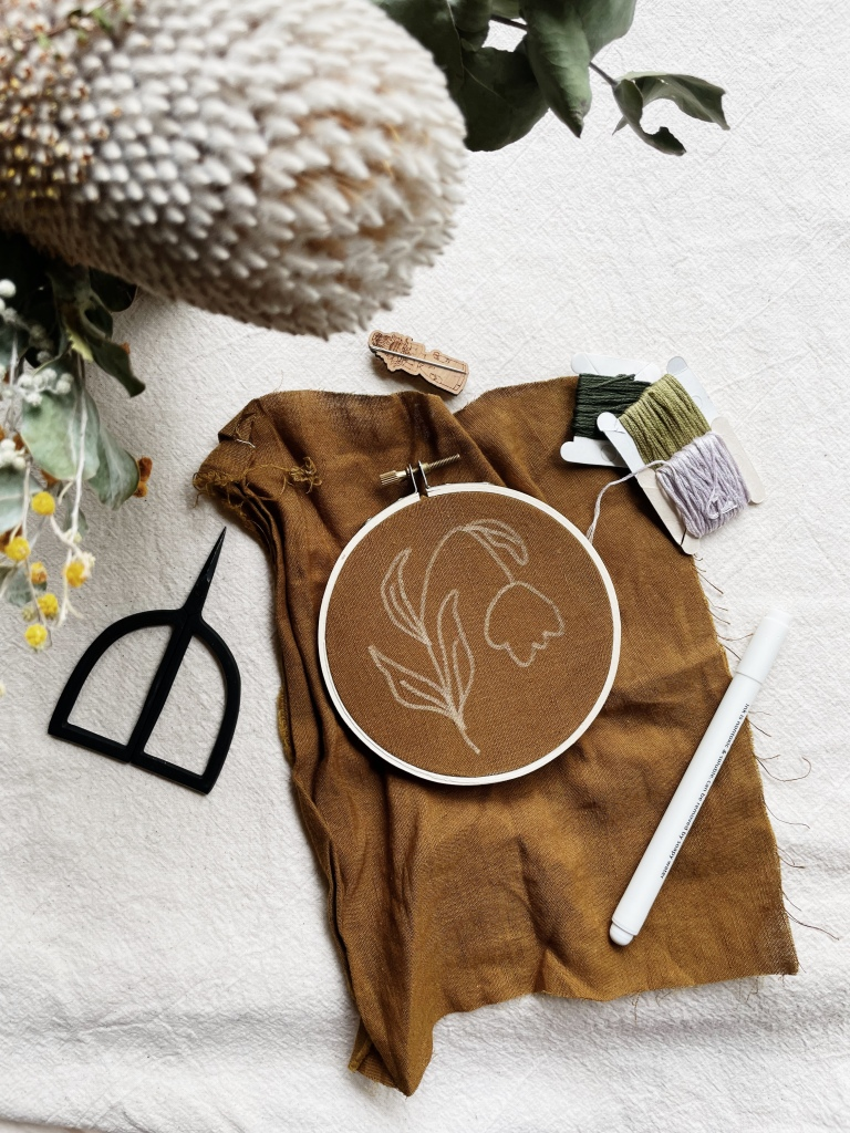 A photo from above of an embroidery hoop sitting on calico background. Mustard brown fabric is in the hoop & a white outline of a flower is drawn on it. Black scissors, a white pen and three thread cards sit around the hoop.